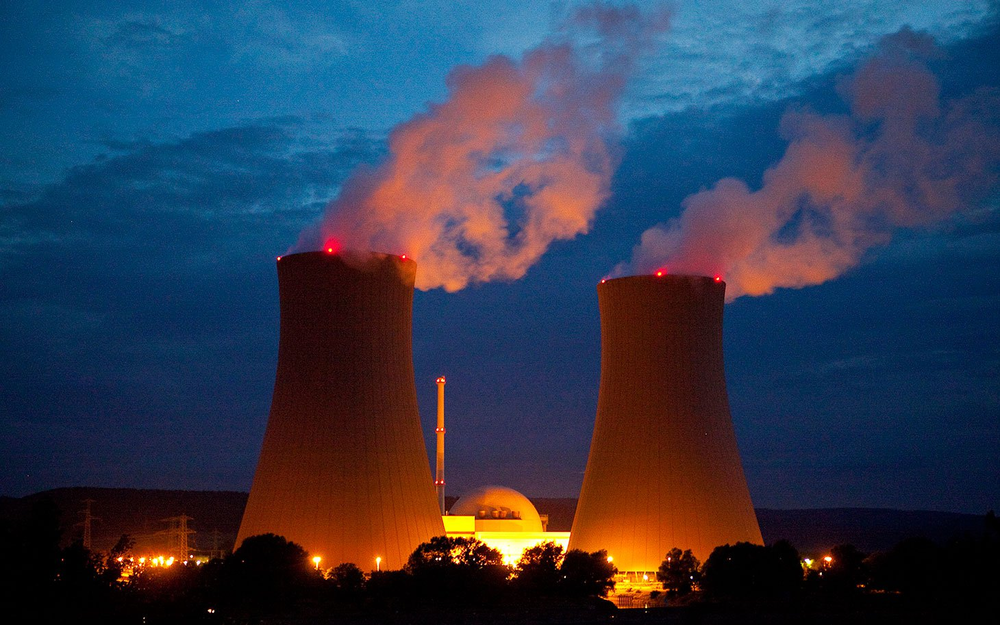 Cooling towers emit vapor into the night sky